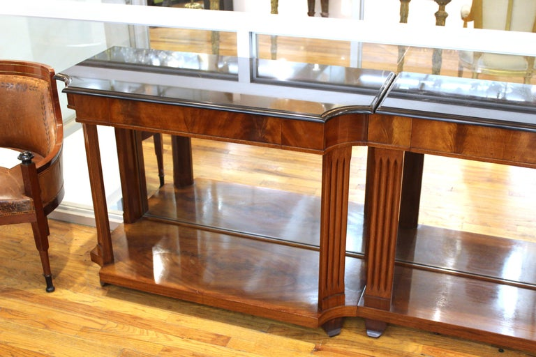 Grosfeld House Empire style flame mahogany mirrored console table in three segments, black marble tops over drawers and fluted legs. Measures: 33