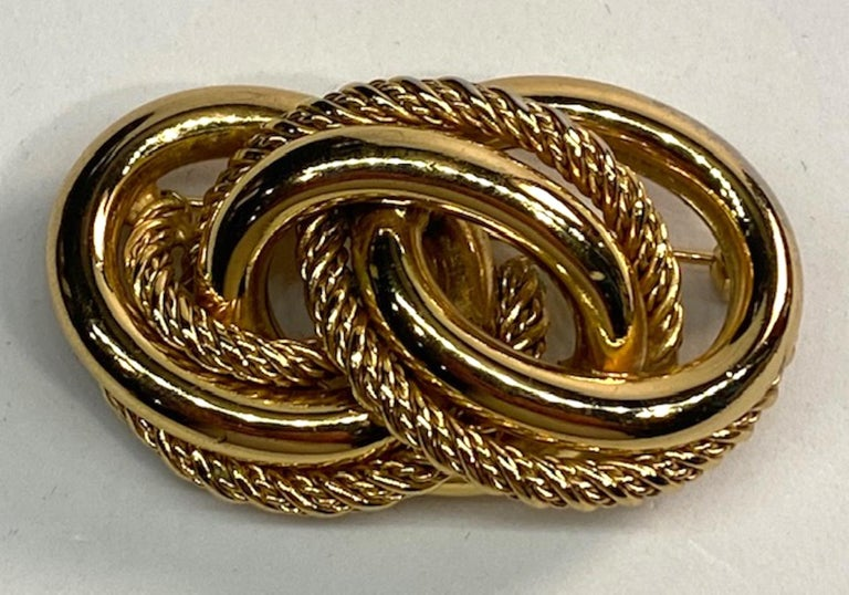 Smooth and twist rope textured interlocking links in gold tone by over 100 year old German jewelry company Grosse. The brooch measures 2 inches wide, 1.35 inches high and .75 of an inch high. Oval signature plaque on the back inscribed with Grosse,