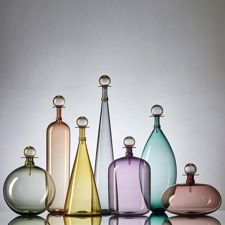 Set of 7 contemporary hand blown glass bottles in an array of smoky colorful forms inspired by geometric decanters of Mid-Century Modern design. Coordinated neck-wrap and blown glass stopper finish each decanter with luminous gold-leaf. Offered in a