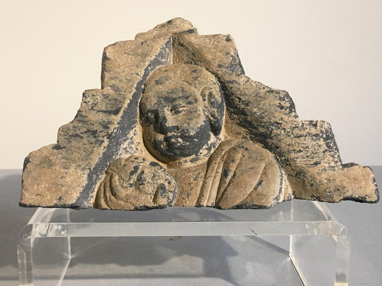 An interesting group of sculptural fragments from the ancient Kingdom of Gandhara, circa 3rd-5th century. The group consists of a triangular shaped fragment with an image of a monk holding up an offering. This image may represent the final scene in
