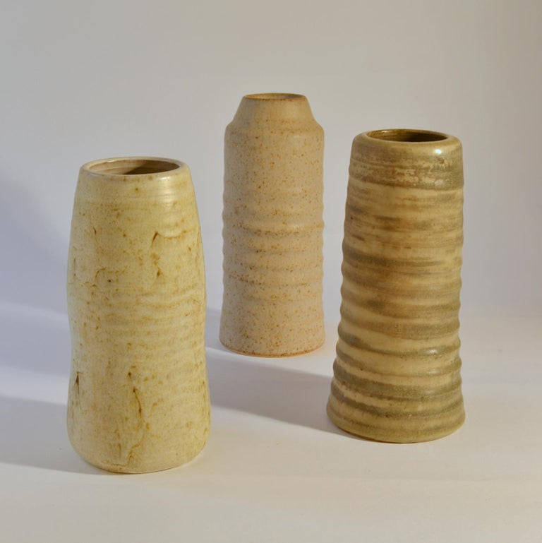 Three-cylinder Studio Pottery vases in white tones are very sculptural with a natural rough character created on the turning wheel by highly technical skilled Dutch ceramist in the 1960s. The glazes made of natural resources are highly influenced by