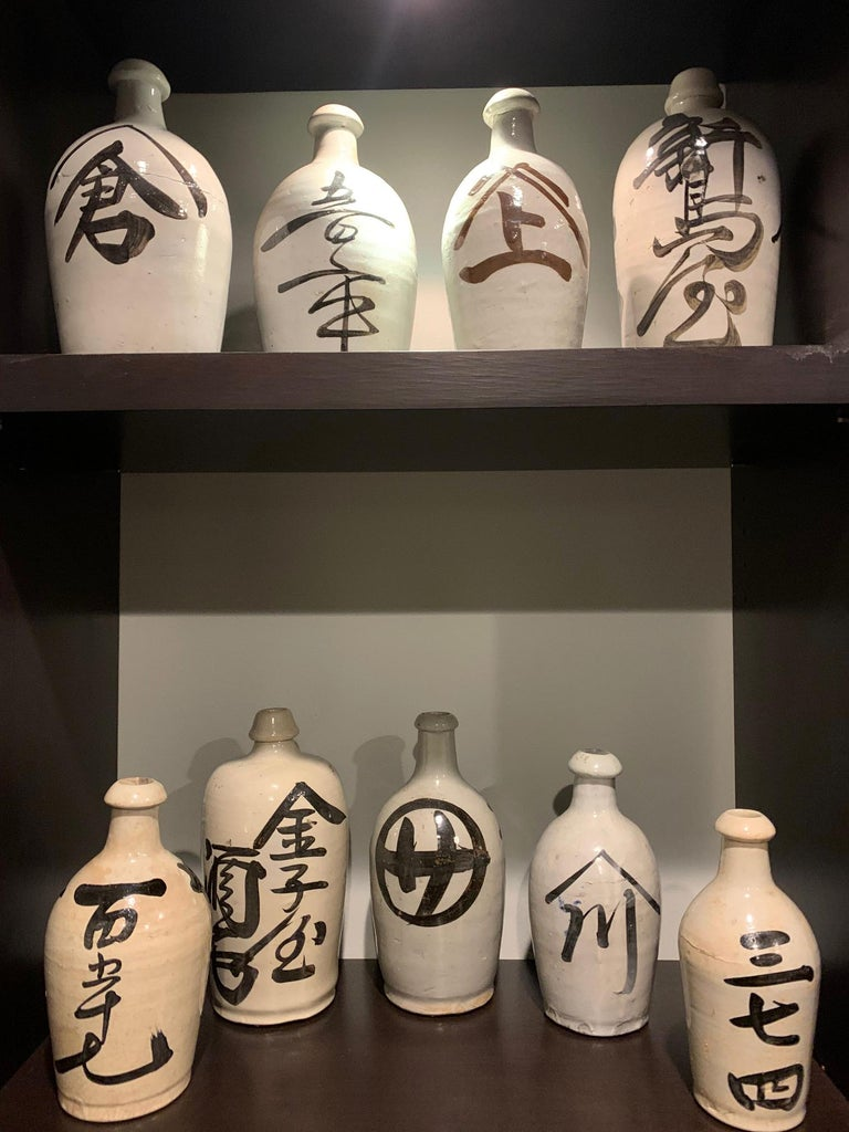 A large collection of nice Japanese stoneware saki bottles circa first quarter of 20th century. Heavily potted, these bottled were dipped in white glaze and brushed on with black Kanji characters to show the brand names of saki. They were likely
