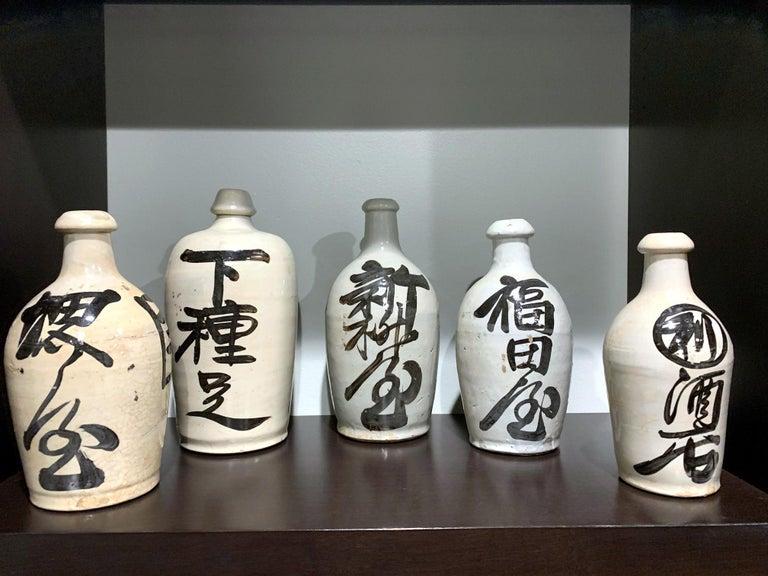 Stoneware Group of Nine Vintage Japanese Saki Bottle For Sale