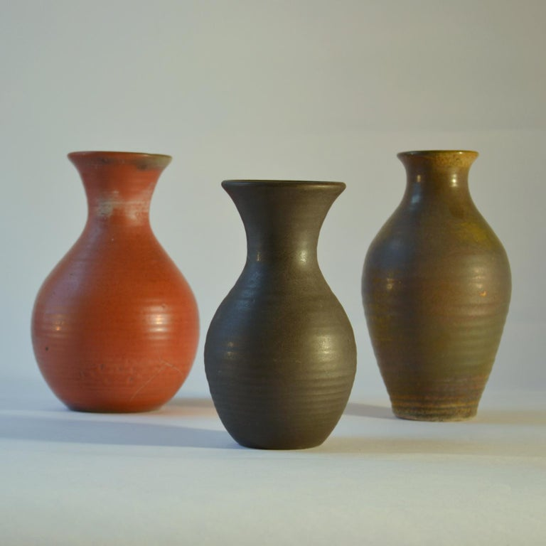 Three Studio Pottery vases in coral red, mat black and moss green are created on the turning wheel by highly technical skilled Dutch ceramist in the 1960s, made by De Olde Kuyk (DOK) Milsbeek, The Netherlands. The glazes in colours and textures from