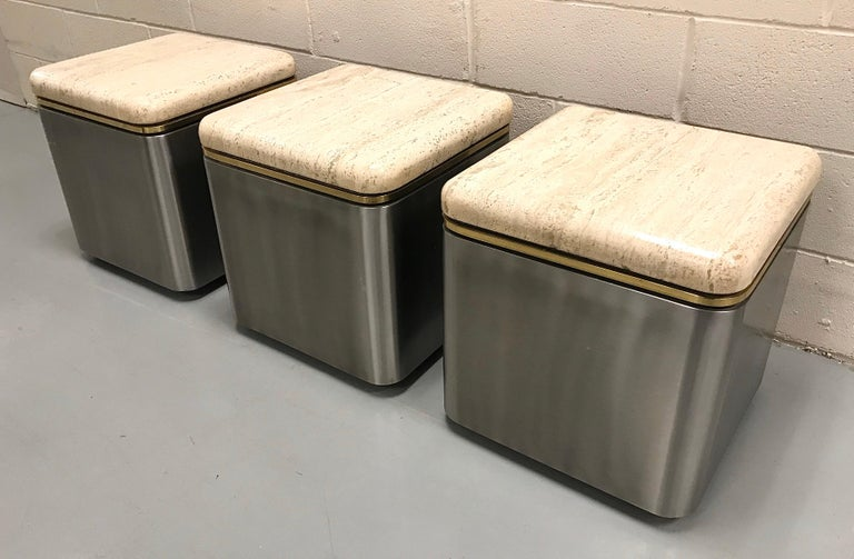 Very well built group of three stainless steel, brass and travertine tables on casters, USA, 1980s.