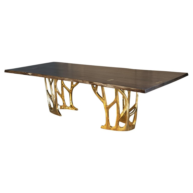 Dining table with cast bronze base and live edge hardwood, stone, concrete or glass top. Can be custom sized and finished.