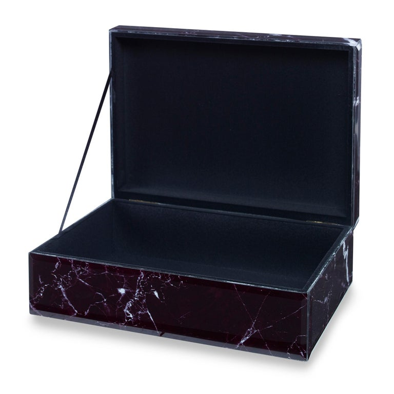 A hinged box featuring a glass facade finished to resemble black marble with white veining.