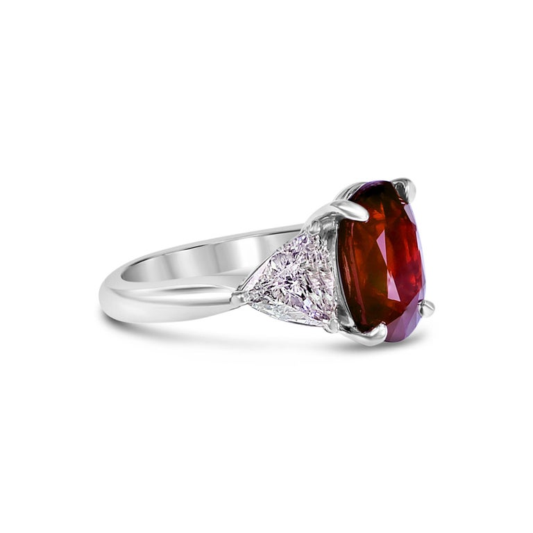 A beautiful 4.26 carat vivid red ruby from Mozambique is set along with 1.09 carats of D color VVS clarity Trillion Pair in this PT 900 wedding ring. Ever classical and a great investment piece, this piece is  a head turner. The details of the ring