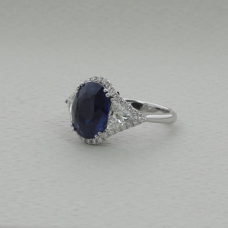 An amzing Blue Sapphire Ring weighing 5.07 carats.  The stone's shape is oval, having for colors a striking Blue.  The ring is with two Troidia Diamond weighing 0.65 Carats and 36 Round Diamonds weighing 0.30 Carats.  The Sapphire is accompanied by