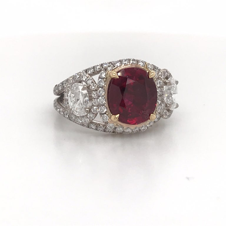 GRS Certified ring featuring one oval shape natural Ruby weighing 2.57 carats flanked with two diamond ovals and numerous round brilliants.  Ruby: Dimension: 8.84 x 7.80 x 3.89 mm Color: Vivid Red Pigeon Blood No Heat  Please email for more rubies.