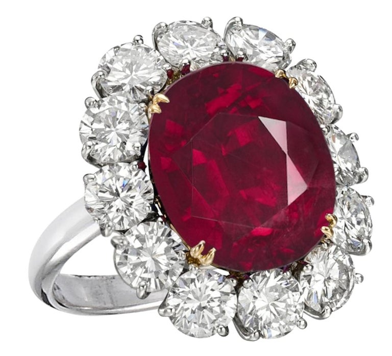 An exquisite 5 carat vivid blood red purple oval no-heat ruby commands attention in this extraordinary 18 carats yellow gold and platinum classic ring.   A halo of approximately 1 carats of bright white (E/F) and near-flawless (VS1) diamonds