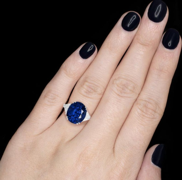 An absolutely exquisite engagement ring featuring a royal blue oval sapphire set in a four claw open back setting weighing a total of 5.58 carats.  The centre stone is accompanied by two trillion shaped diamond on either side and they weight