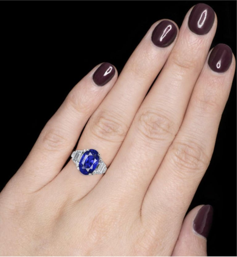 Featuring an exquisite vivid untreated unheated blue Ceylon oval-shaped sapphire flanked by trapezoid-shaped diamonds.  Blue sapphire weighing 5.12 carats Diamonds weighing 2 carats Size 7 1/2 Platinum Accompanied by GRS REPORT