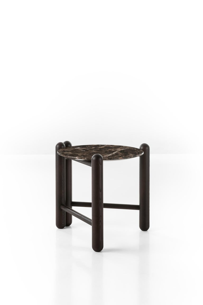 """This table completes and enriches the company's first line of upholstered pieces with sumptuous elegance. The folding structure in ash wood post has a round top available in such precious materials as """"Emperador Brown"""" marble or glass """"Stopsol"""" ,"""