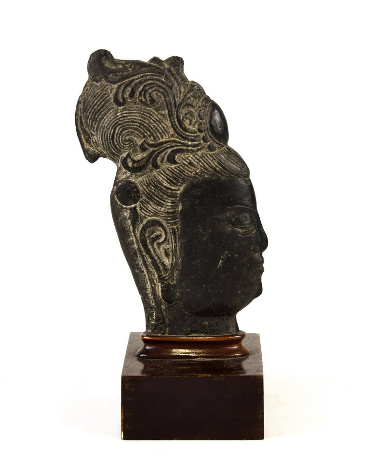 Guanyin's Head is a charming gray-black stone sculpture by an anonymous Chinese master of the 20th century.  Depicting the profile of the divinity's head with the hairstyle in low and high relief, this oriental sculpture has the base in glued