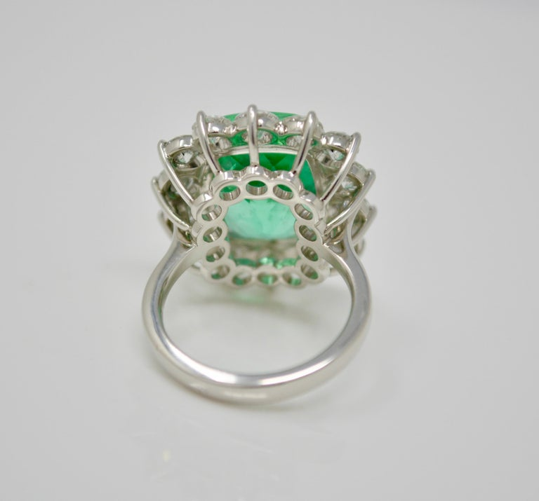 This unique creation by Moguldiam Inc features a Gubelin certified 10.76 carat columbian cushion shaped luscious green emerald surrounded by  beautiful white circular cut diamonds. This is a beautiful and vibrant  columbian emerald. The fourteen