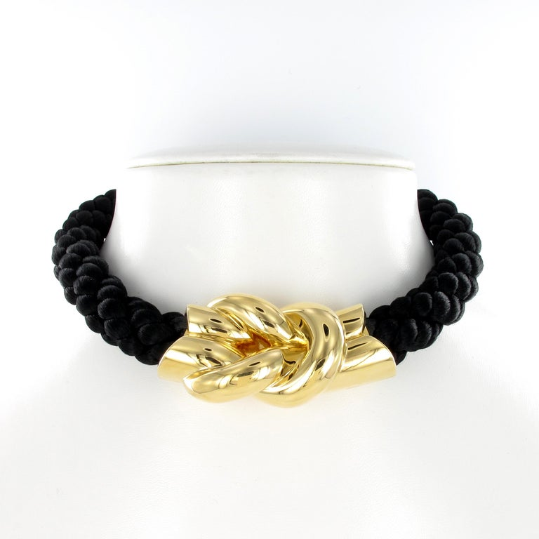 This choker by Gubelin features a bold square (reef) knot in 18 karat yellow gold. The necklace consists of artfully plaited black ropes.  Length: 40 cm / 15.74 inches Signed Gubelin and hallmarked 750 for 18 karat gold.
