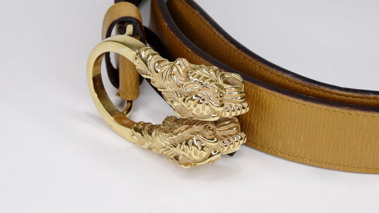 Score yourself a piece of classic Gucci with this amazing belt! Circa 1980s, this light brown leather belt features a Dionysus antiqued gold buckle-a unique detail referencing the Greek god Dionysus, who in myth is said to have crossed the river