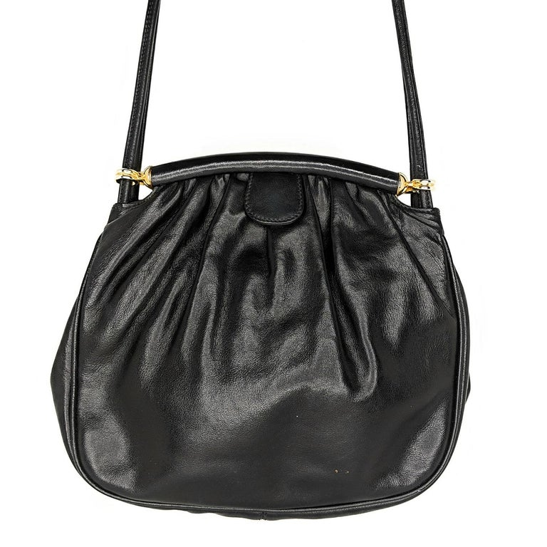 Black Calf leather Gucci shoulder bag with antique gold-tone hardware, long flat shoulder strap that can be worn on the shoulder or cross the body, tonal leather and nylon lining with one zip pocket and a snap closure.  Designer: Gucci Material: