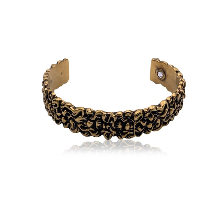 Beautiful cuff bracelet by Gucci. Made in aged gold-tone metal. It features a stunning engraved lion's mane motif . Clear crystal detail set internally. Size: S. Inner circumference: 6.5 inches - 16.5 cm. Inner diameter: 2.25 inches - 5.8 cm. Width: