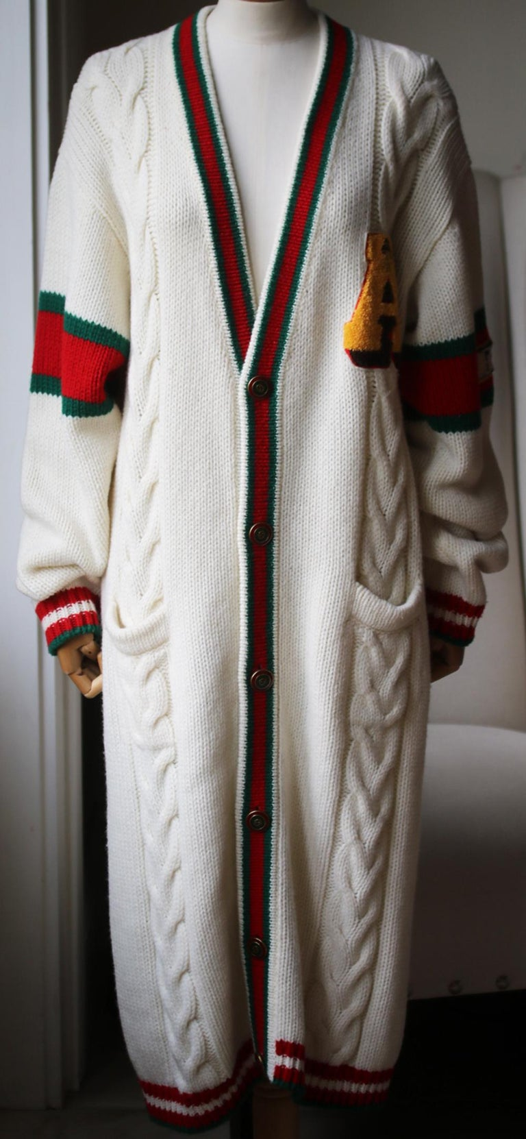 Seen on the runway, this sumptuous cable-knit wool cardigan is detailed with the label's signature green and red webbing and turns to reveal a signature tiger appliqué and the label's tongue-in-cheek 'Guccy' lettering. Cream, green and red wool.