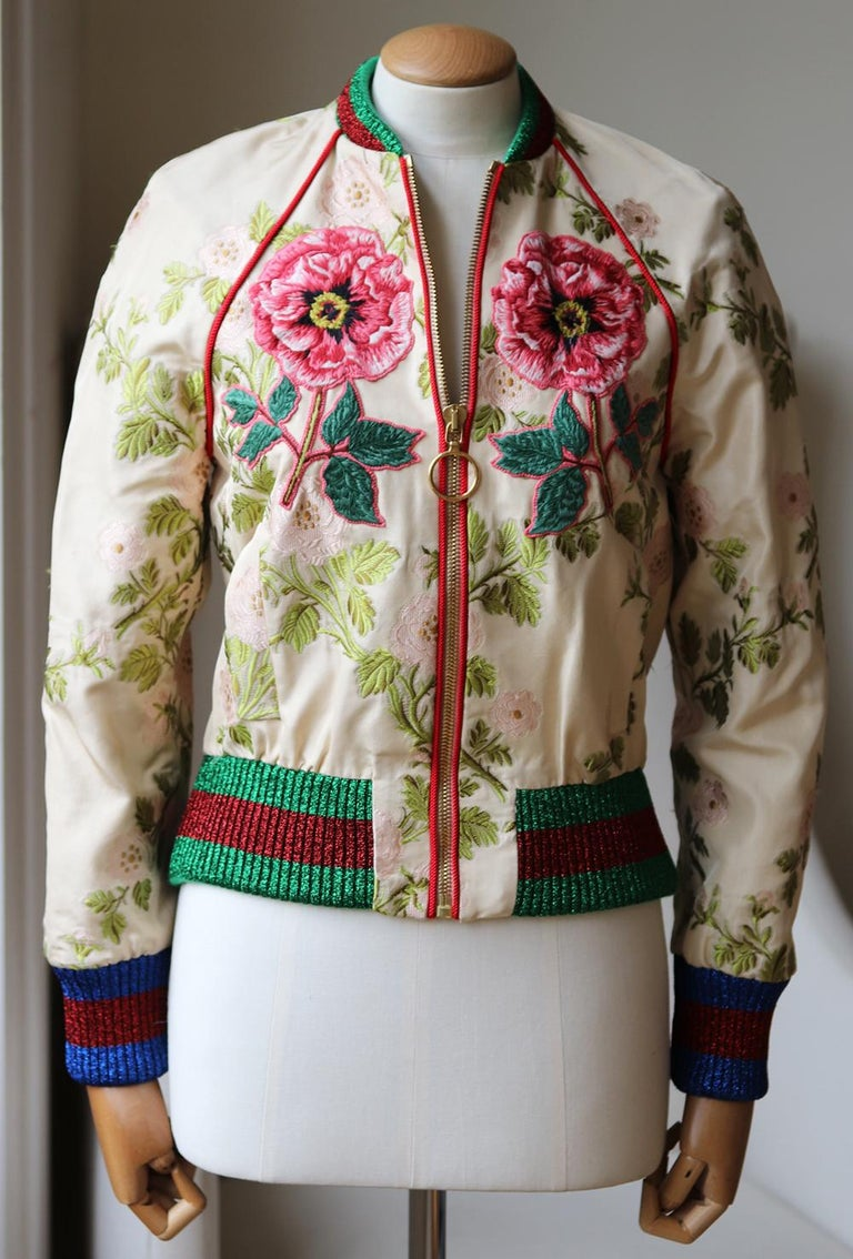Gucci's statement bomber jackets have been a key feature of every season as they are easy to dress up or down. Designed with the brand's signature metallic blue and red ribbed trims, this silk floral brocade style is decorated with appliqués in a