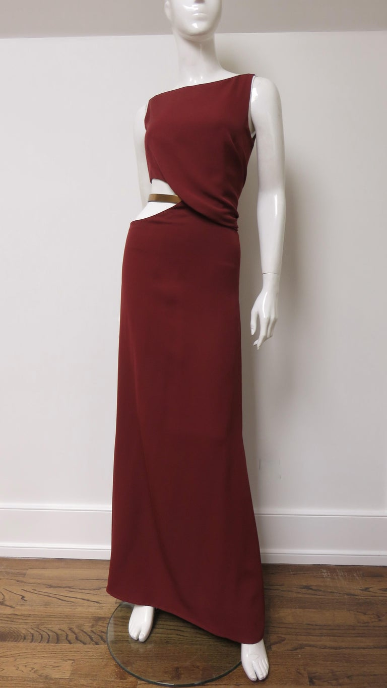 A gorgeous dress, gown from Gucci in burgundy silk.  It is sleeveless with a circular cut out at one side of the waist highlighted with a gold leather adjustable Gucci belt across it and subtle draping at the other side.  The back dips close to the