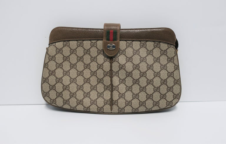 A vintage classic authentic Gucci clutch handbag featuring its iconic 'G' tan canvas, tan/brown leather trim and piping, red and green racing stripe, and two-tone metal Gucci logo. Marked 'Gucci' and 'Made in Italy' on interior leather tag (see