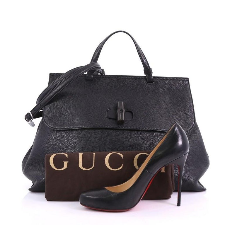 160834e02340 This Gucci Bamboo Daily Top Handle Bag Leather Large, crafted from black  leather, features