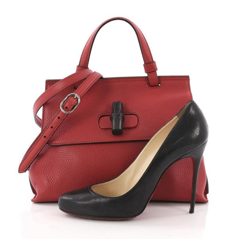 This Gucci Bamboo Daily Top Handle Bag Leather Small, crafted from red leather, features flat top handle, and silver-tone hardware. Its flap with bamboo turn-lock closure opens to a multicolor fabric interior with zip and slip pockets. **Note: Shoe
