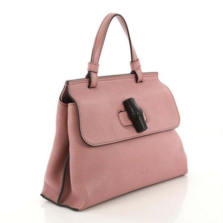 This Gucci Bamboo Daily Top Handle Bag Leather Small, crafted from pink leather, features a flat top handle and silver-tone hardware. Its flap with bamboo turn-lock closure opens to a beige printed fabric interior with zip and slip pockets.