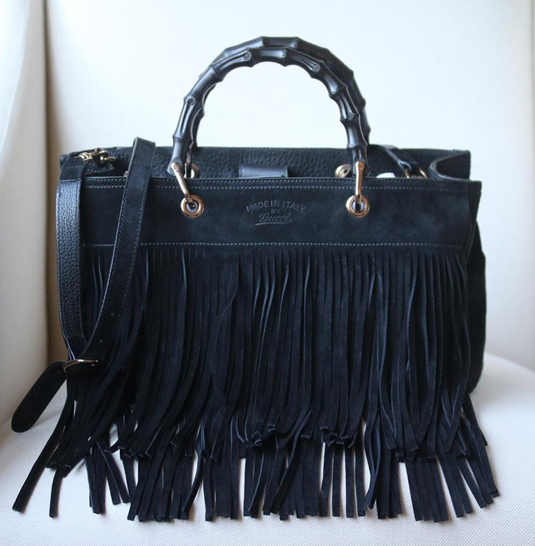 Gucci's Italian-made suede bag features the brand's signature bamboo handle along the top, extra long fringing and tassels. Black suede (Calf). Adjustable shoulder strap. Bamboo handles, fringed suede trim, designer stamp, silver-tone hardware. Two
