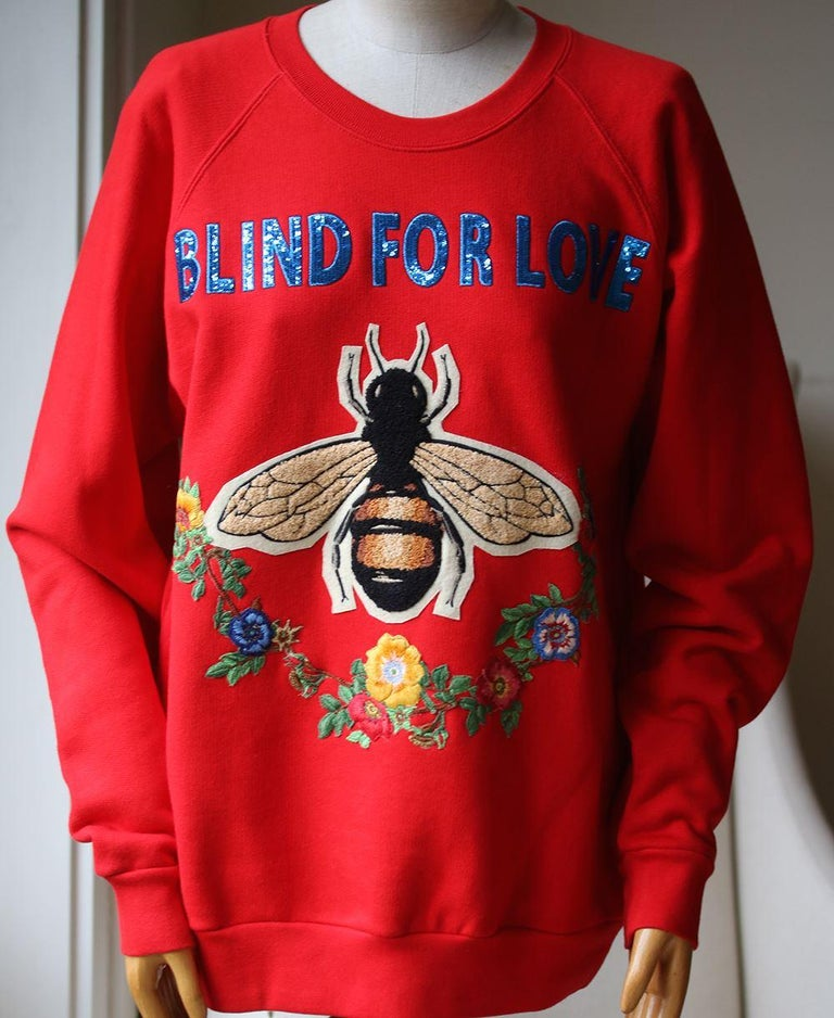 The sweatshirt, an essential cut carried season to season, features embroidered appliqués representing several symbolic Gucci motifs, including the bee surrounded by a garland of flowers. Blind for Love