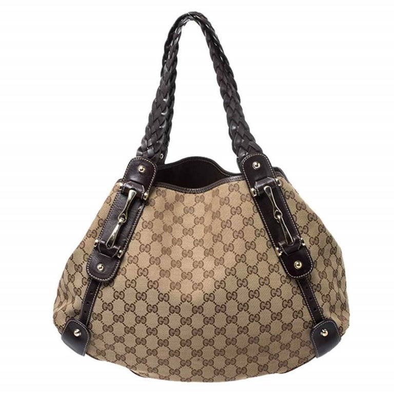 Take your style a notch higher with this Pelham shoulder bag from Gucci. Cut out from the brand's signature GG canvas and leather, it comes in beige and brown hues. The bag features two braided leather handles, a spacious fabric interior, and