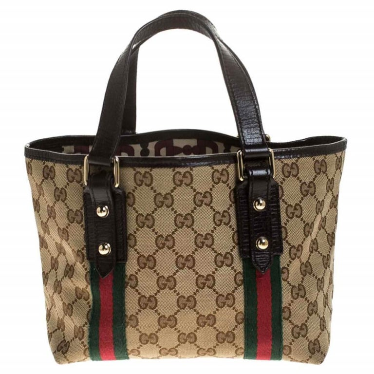 Flaunt your chic style with this mini Jolicoeur web tote from Gucci! Coated in GG canvas, the bag is accented with signature web trims, dual top handles, and gold-tone charms. It has a fabric-lined interior, equipped with a spacious compartment to