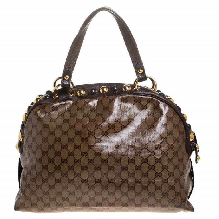This chic Gucci Babouska bag might just become the most-loved in your closet. Crafted from GG crystal canvas, it has gold-tone stud detailing and the heart emblem on the front. The bag is equipped with two handles and a spacious fabric interior for