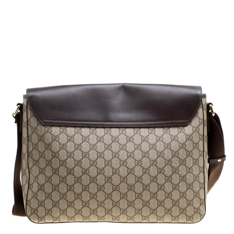 Carry your essentials in style in this Gucci messenger bag. It has been crafted in a combination of brown leather and beige GG supreme canvas. The brown leather flap features embossed brand detail and opens to a canvas-lined interior that further