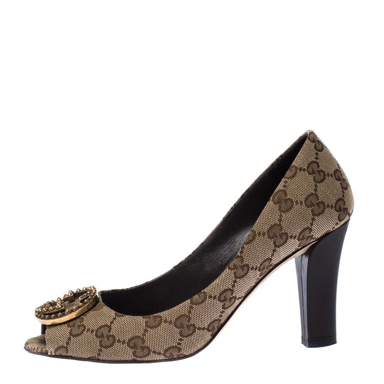 Made by Gucci, this pair of pumps is the perfect mix of comfort and style. Crafted out of GG canvas, these pumps are adorned with embellished GG logo on the vamps. Make a fabulous statement while donning this pair of beige/brown pumps.  Includes: