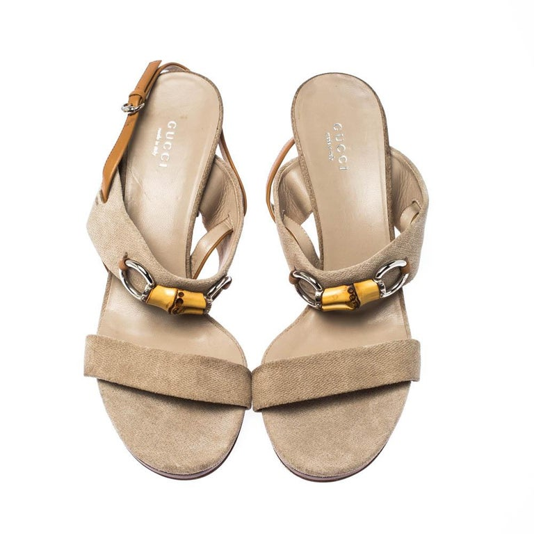 Slip into these Gucci sandals and add grace to your strides. Crafted from beige canvas, these slingbacks feature bamboo Horsebit details. With open toes and 9 cm heels, these sandals will give a feel of luxury to your feet.  Includes: The Luxury
