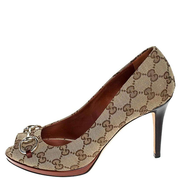 These beige Gucci peep-toe pumps speak classic style. Crafted in signature GG canvas, the pumps feature horsebit detailing in gold-tone. Pair these pumps with your favorite formal outfit for a high style at work!  Includes: Original Dustbag