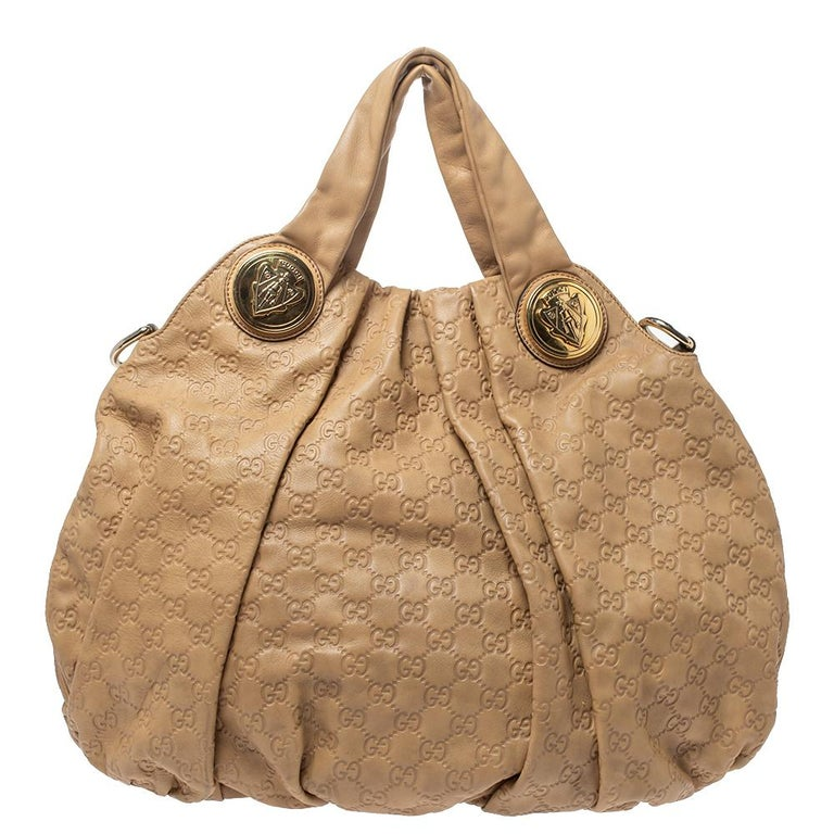 This Gucci hobo is built for everyday use. Crafted from Guccissima leather, it has a beige exterior and two handles for you to easily parade it. The fabric insides are sized well and the hobo is complete with the signature emblems.  Includes: