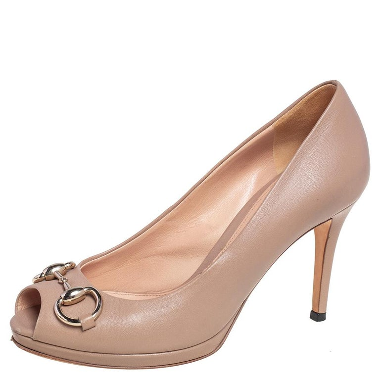 These Gucci beauties are crafted from beige leather and feature a peep-toe design. They flaunt gold-tone signature Horsebit detailing on the front, have comfortable leather-lined insoles, and are complete with slender heels.