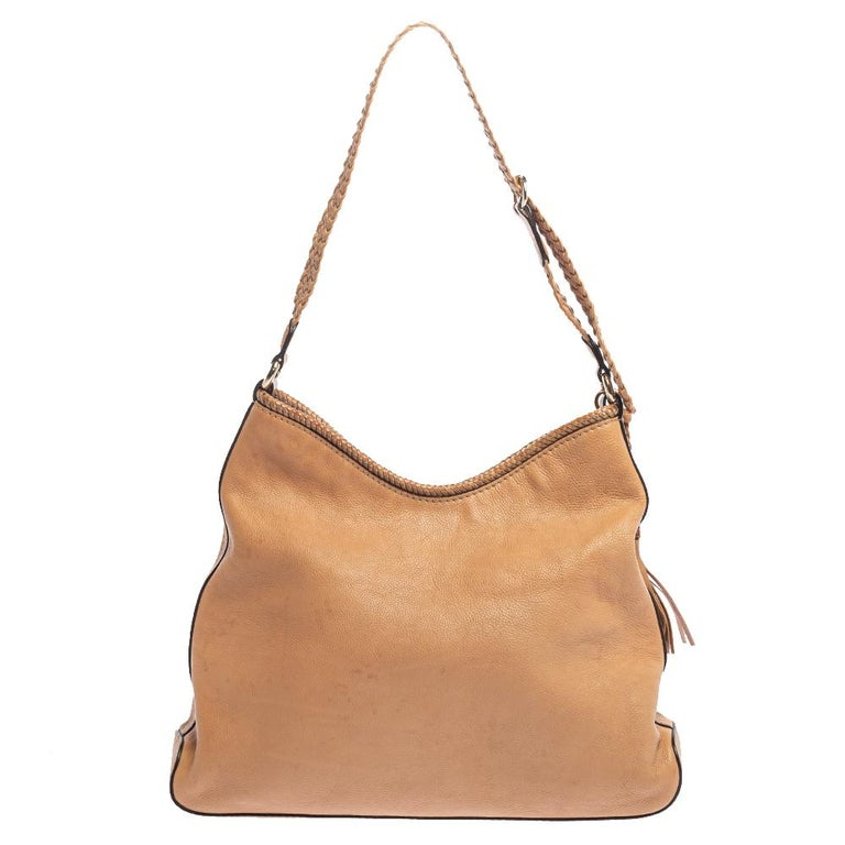 This Gucci Marrakech hobo is crafted from beige leather. It features a snap button fastening and a well-sized canvas interior. The bag is finished with tassel detailing on the side and a braided handle; and overall, it has a beautiful appeal.