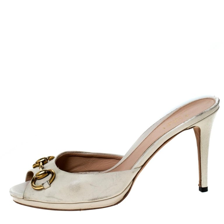 Finesse and poise will all come naturally to you when you step out in this pair of New Hollywood slides from Gucci. Crafted from beige leather, the slides have been styled with the iconic Horsebit detail at the front and stiletto heels. The insoles