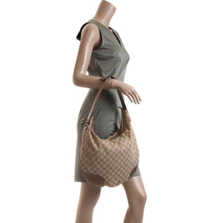 This stunning Beige Heart Bit Hobo by Gucci is ready to glam up your outfit! Crafted from shimmering GG fabric with contrasting leather trim, this handbag is accented with a Gucci gold heart with bamboo detailing and half horsebit charms, a