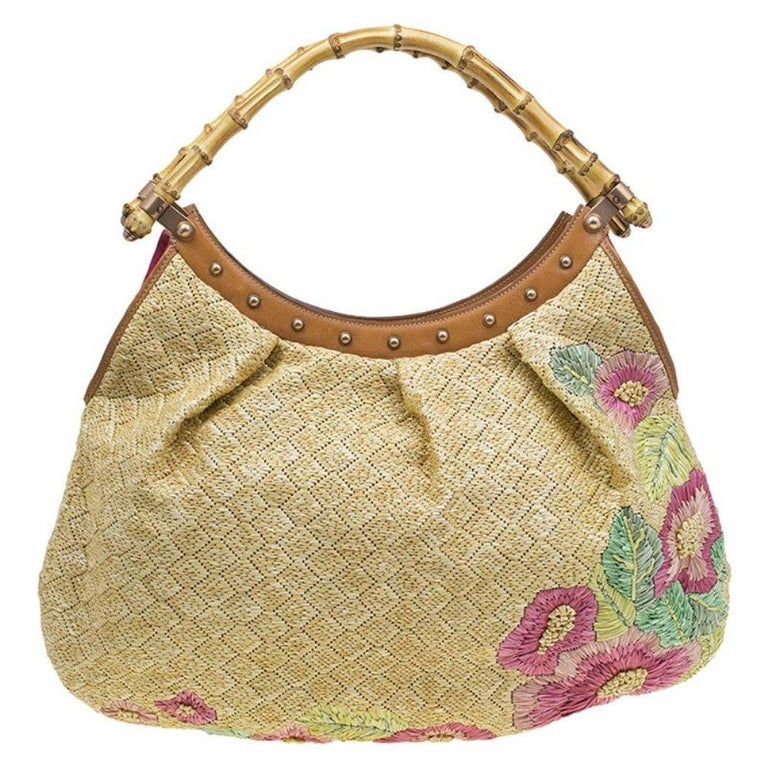 Redefining luxury for the 21st century, Gucci is one of the most well-known luxury fashion brands. Smart and feminine, this hobo is crafted in beige raffia with floral print motifs on the exterior body. It is decorated with dual bamboo handles and