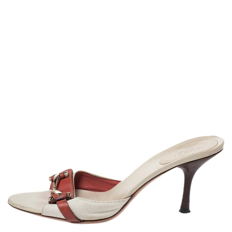 Flaunt these fabulous sandals from Gucci as you step out in style. These canvas and leather sandals feature open toes and a slide design. They bring metal details on the uppers and 8.5 cm heels.  Includes: Original Dustbag
