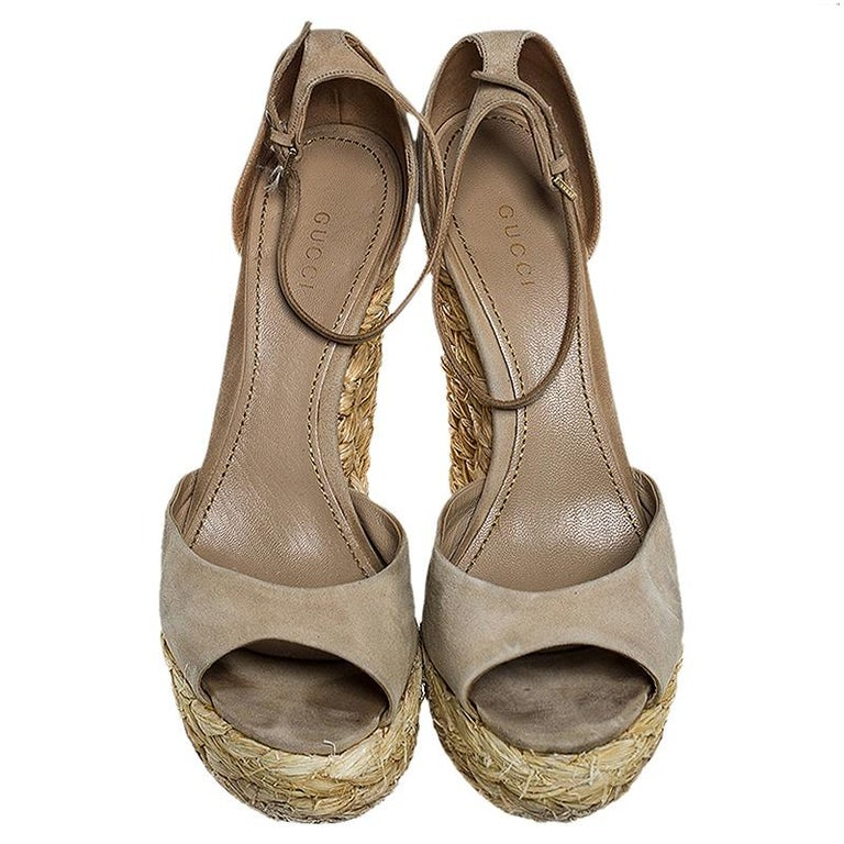 A perfect mix of elegant fashion and comfortable style, these Gucci sandals come crafted from suede and designed with peep toes, ankle straps and closed counters. They're visually stunning and they stand tall on raffia wedge heels.  Includes: