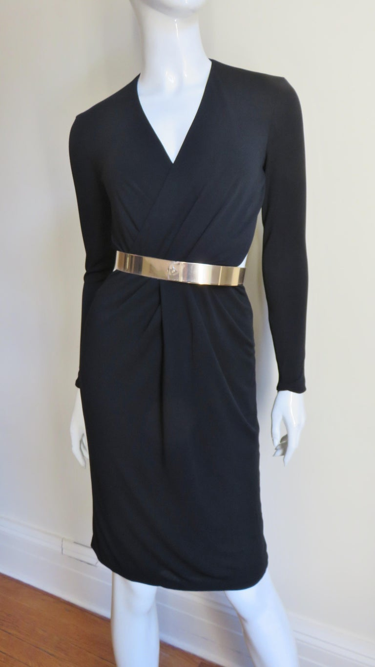 A gorgeous black silk jersey dress from Gucci.  It has a front crossing V neck, long sleeves with zippers and cut outs at the side waist.  The skirt is straight and the back is dramatically cut out from the neck to just below the waist.  It is lined