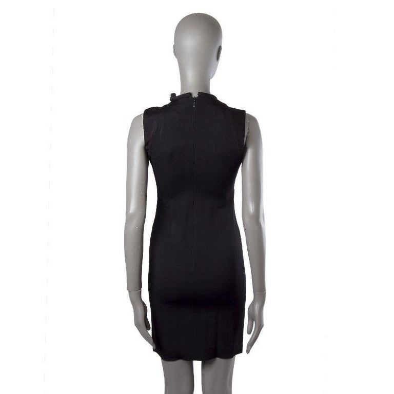 Gucci sheath dress in black acetate (78%) and viscose (32%). With piped crew neck that ties on the side, application on the front of the neck in golden metal, and slit on one shoulder. Closes with one hook and invisible zipper on the back. Lined in